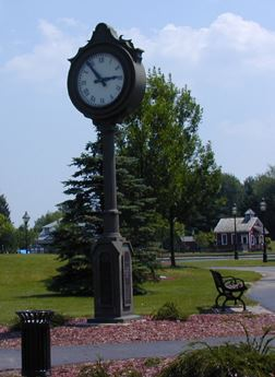 A large clock standing in a park.