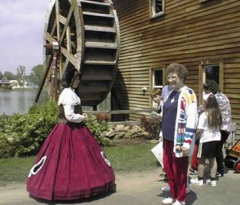 A woman in old style garb leading a tour group.